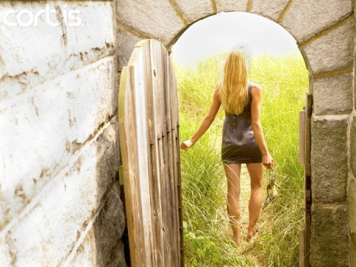 Woman Walking Through Door into Meadow